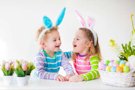 Happy children celebrate Easter at home. Boy and girl wearing bunny ears enjoying egg hunt. Kids playing with color eggs and flower basket. Spring crafts and art for toddler child and preschooler kid. Stock Photo