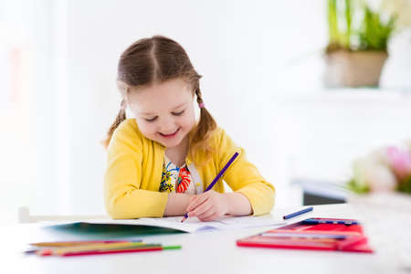 preschoolers: Cute little girl doing homework, reading a book, coloring pages, writing and painting. Children paint. Kids draw. Preschooler with books at home. Preschoolers learn to write and read. Creative toddler Stock Photo