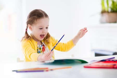 Schattig meisje doet huiswerk, het lezen van een boek, kleurplaten, schrijven en schilderen. Kinderen schilderen. Kinderen tekenen. Kleuter met boeken thuis. Kleuters leren lezen en schrijven. Creative peuter