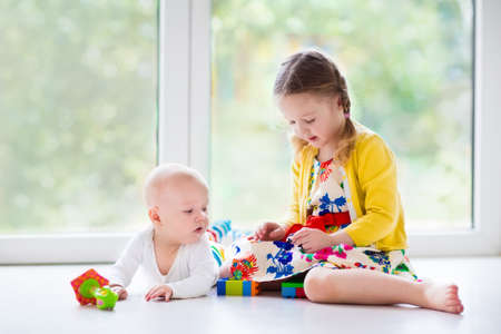 Kids playing together at home. Little girl and boy play sitting on the floor next to a window. Toddler child building tower with colorful blocks. Baby starting to crawl. Toys for young children. Фото со стока