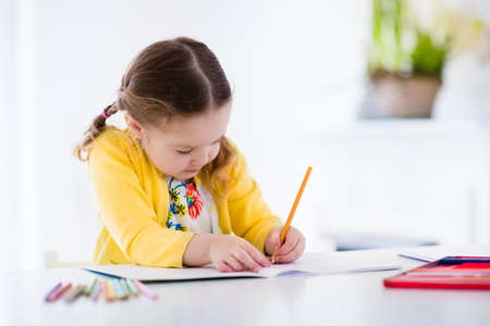 Cute little girl doing homework, reading a book, coloring pages, writing and painting. Children paint. Kids draw. Preschooler with books at home. Preschoolers learn to write and read. Creative toddler Banque d'images
