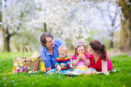 Family with children enjoying picnic in spring garden. Parents and kids having fun eating lunch outdoors in summer park. Mother, father, son and daughter eat fruit and sandwiches on colorful blanket. Stock Photo