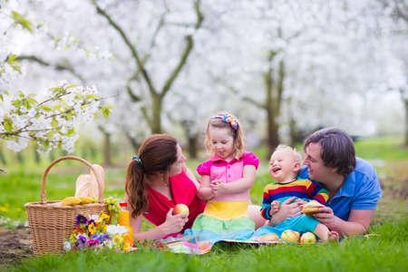 Familien mit Kindern Picknick im Frühjahr Garten genießen. Eltern und Kinder, die Spaß Essen Mittagessen im Freien im Sommer Park. Mutter, Vater, Sohn und Tochter essen Obst und Sandwiches auf bunten Decke.