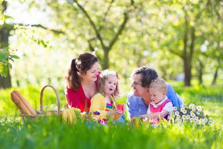 familie: Familien mit Kindern Picknick im Frühjahr Garten genießen. Eltern und Kinder, die Spaß Essen Mittagessen im Freien im Sommer Park. Mutter, Vater, Sohn und Tochter essen Obst und Sandwiches auf bunten Decke. Lizenzfreie Bilder