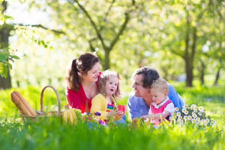 Family with children enjoying picnic in spring garden. Parents and kids having fun eating lunch outdoors in summer park. Mother, father, son and daughter eat fruit and sandwiches on colorful blanket. Stok Fotoğraf