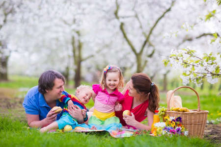 Family with children enjoying picnic in spring garden. Parents and kids having fun eating lunch outdoors in summer park. Mother, father, son and daughter eat fruit and sandwiches on colorful blanket.