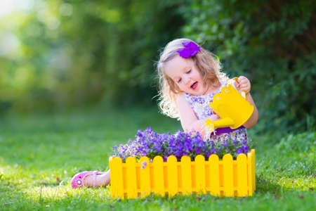 water garden: Child working in the garden. Kids gardening. Children watering flowers. Little girl with water can on a green lawn in the backyard in summer. Toddler kid playing outdoors planting purple flower pots.