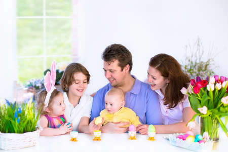 a little dinner: Happy young family with three children - teenager boy, cute little toddler girl with bunny ears and a newborn baby - enjoying Easter breakfast in a white sunny dining room with a big garden window Stock Photo