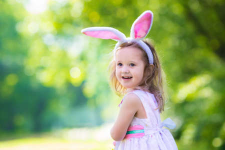 conejo: Niña que se divierte en la búsqueda de huevos de Pascua. Los niños en orejas de conejo y traje de conejo. Los niños con coloridos huevos en una cesta. Hijo del niño que juega al aire libre. Niño que sostiene la tarjeta blanca en blanco para el texto.