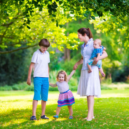 school age boy: Happy family with three kids in a park. Young mother with children, little toddler girl, school age boy and baby playing in a sunny summer garden, walking and holding hands with her son and daughter.