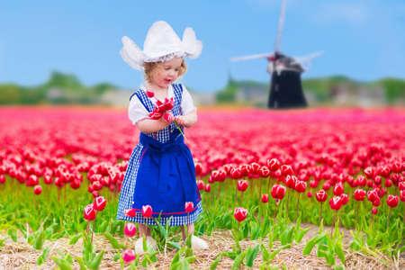 tulipan: Urocza dziewczyna maluch sobie kręcone tradycyjny strój narodowy holenderski kostium i kapelusz odtwarzanie w dziedzinie kwitnących tulipanów obok wiatraka w regionie Amsterdam, Holandia, Holandia