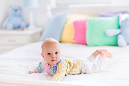 tummy: Baby boy in white bedroom. Newborn child in bed with pastel color cushions. Nursery for children. Textile, pillows and bedding for kids. Family morning at home. New born kid tummy time with toy bear.