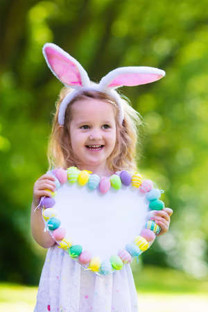 basket: Little girl having fun on Easter egg hunt. Kids in bunny ears and rabbit costume. Children with colorful eggs in a basket. Toddler kid playing outdoor. Child holding blank white board for your text.
