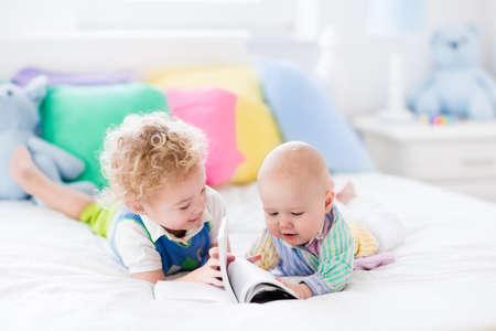 nursery: El muchacho del niño y del bebé que lee un libro en la cama de los padres. Los niños leen libros en el dormitorio blanco. Niños jugando juntos. Los hermanos de unión. juguetes de vivero y textiles en colores pastel. Hermanos besan, se abrazan. Foto de archivo