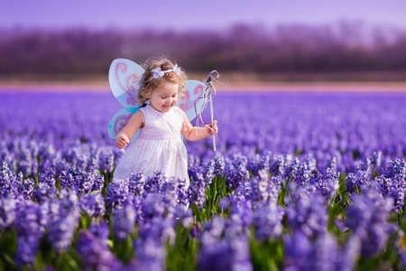 かわいい巻き毛少女が翼およびオランダのヒヤシンスのフィールドで遊ぶ魔法の杖で花冠と妖精コスチューム。紫の花で実行の子。子供の園芸しま