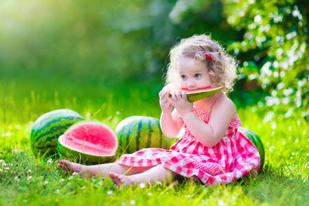 Child eating watermelon in the garden. Kids eat fruit outdoors. Healthy snack for children. Little girl playing in the garden holding a slice of water melon. Kid gardening. Archivio Fotografico