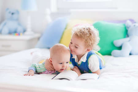 newborn animal: Toddler boy and baby reading a book in parents bed. Children read books in white bedroom. Kids playing together. Siblings bonding. Nursery toys and textile in pastel colors. Brothers kiss and hug.
