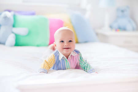 nursery room: Baby boy in white bedroom. Newborn child in bed with pastel color cushions. Nursery for children. Textile, pillows and bedding for kids. Family morning at home. New born kid tummy time with toy bear.