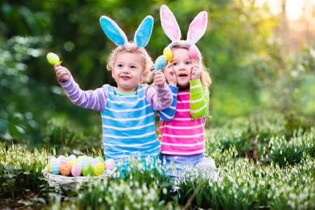 Kinder auf Ostereiersuche Frühlingsgarten in Blüte. Kinder mit Hasenohren für bunte Eier im Schnee fallen Blumenwiese suchen. Kleinkind Jungen und Vorschüler Mädchen im Kaninchenkostüm draußen spielen. Standard-Bild