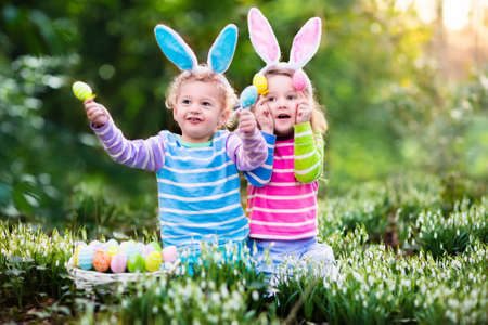 huevos de pascua: Niños en búsqueda de huevos de Pascua en jardín floreciente primavera. Los niños con orejas de conejo en busca de huevos de colores en la caída de la nieve prado de flores. El muchacho del niño y la niña de edad preescolar en traje de conejo jugar al aire libre.