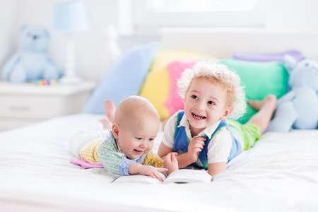 부모 침대에서 책을 읽고 유아 소년과 아기. 아이들은 화이트 침실에서 책을 읽고. 아이들은 함께 연주. 형제는 결합. 파스텔 색상 보육 장난감, 섬유.
