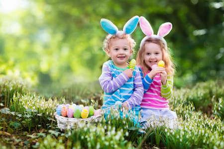 gemelas: Niños en búsqueda de huevos de Pascua en jardín floreciente primavera. Los niños con orejas de conejo en busca de huevos de colores en la caída de la nieve prado de flores. El muchacho del niño y la niña de edad preescolar en traje de conejo jugar al aire libre.