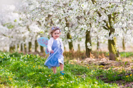 Little girl in fairy costume with wings, flower crown and magic wand playing in blooming apple tree garden on Easter egg hunt. Kid watching cherry blossom in the garden. Child in spring fruit orchard.