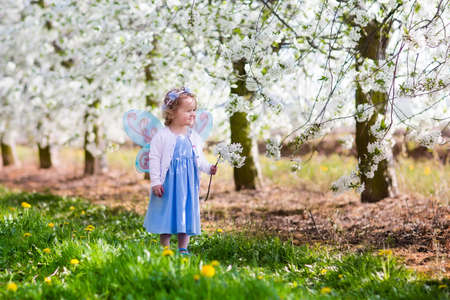 fairy garden: Little girl in fairy costume with wings, flower crown and magic wand playing in blooming apple tree garden on Easter egg hunt. Kid watching cherry blossom in the garden. Child in spring fruit orchard. Stock Photo