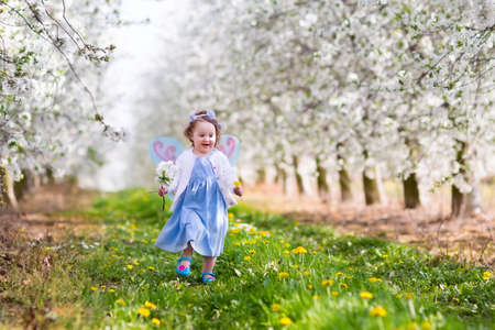 Little girl in fairy costume with wings, flower crown and magic wand playing in blooming apple tree garden on Easter egg hunt. Kid watching cherry blossom in the garden. Child in spring fruit orchard. Foto de archivo