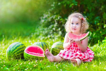 Kind essen Wassermelone im Garten. Kids Obst essen im Freien. Gesunder Snack für Kinder. Kleine Mädchen spielen im Garten, die eine Scheibe der Wassermelone. Kid im Garten.