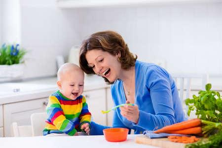 niños sentados: La madre de alimentación infantil. En primer alimento sólido para chico joven. zanahoria orgánica fresca para el almuerzo de verduras. el destete del bebé. Madre y el niño pequeño comer verduras. la nutrición saludable para los niños. Padres alimentan a los niños.