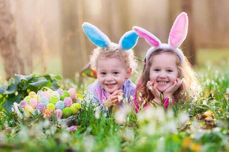 Niños en búsqueda de huevos de Pascua en jardín floreciente primavera. Los niños con orejas de conejo en busca de huevos de colores en la caída de la nieve prado de flores. El muchacho del niño y la niña de edad preescolar en traje de conejo jugar al aire libre. Foto de archivo