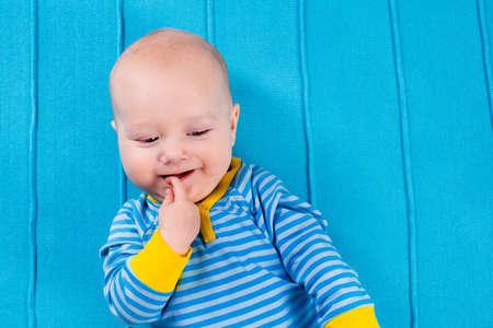 bebé lindo en la manta tejida azul. Dentición infantil juega con el juguete colorido. El niño pequeño en la cama después de la siesta. Ropa de cama y textiles para el cuarto de niños y niños pequeños. Los niños duermen desgaste. niño recién nacido en casa.