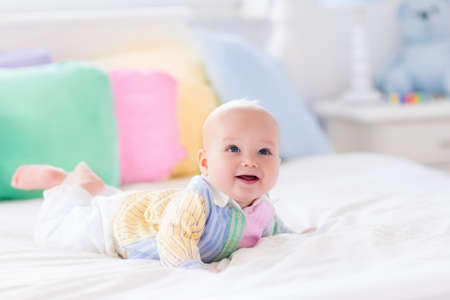 Baby boy in white bedroom. Newborn child in bed with pastel color cushions. Nursery for children. Textile, pillows and bedding for kids. Family morning at home. New born kid tummy time with toy bear.