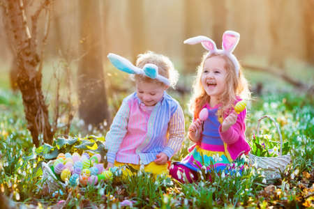 toddler: Kids on Easter egg hunt in blooming spring garden. Children with bunny ears searching for colorful eggs in snow drop flower meadow. Toddler boy and preschooler girl in rabbit costume play outdoors.