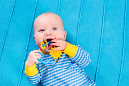 infant: Cute baby on blue knitted blanket. Teething infant playing with colorful toy. Little boy in bed after nap. Bedding and textile for nursery and young children. Kids sleep wear. Newborn child at home.