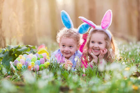 Niños en búsqueda de huevos de Pascua en jardín floreciente primavera. Los niños con orejas de conejo en busca de huevos de colores en la caída de la nieve prado de flores. El muchacho del niño y la niña de edad preescolar en traje de conejo jugar al aire libre.