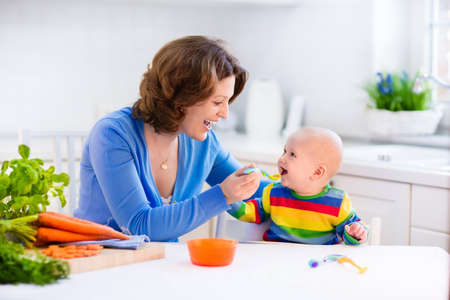 baby chair: Mother feeding child. First solid food for young kid. Fresh organic carrot for vegetable lunch. Baby weaning. Mom and little boy eat vegetables. Healthy nutrition for children. Parents feed kids.