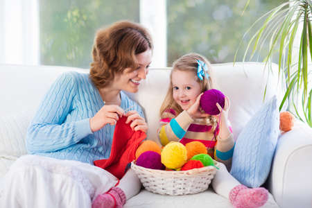 Mother and daughter knitting woolen scarf. Mom teaching child to knit. Crafts and hobby for parents and kids. Toddler girl kid with wool yarn in a basket. Knitted clothing for family with children. Stock Photo