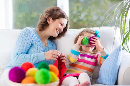 sweater girl: Mother and daughter knitting woolen scarf. Mom teaching child to knit. Crafts and hobby for parents and kids. Toddler girl kid with wool yarn in a basket. Knitted clothing for family with children. Stock Photo