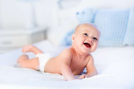 Baby-Junge trägt Windel in weißen sonnigen Schlafzimmer. Neugeborenes Kind im Bett entspannen. Kindergarten für Kinder. Textilien und Betten für Kinder. Familien Morgen zu Hause. Neugeborenes Kind im Bauch Zeit mit Spielzeugbären.