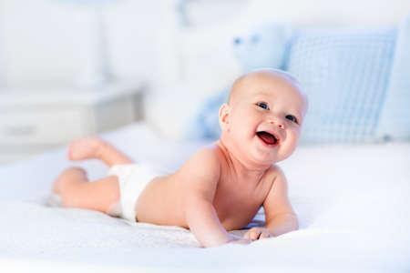 recien nacido: Bebé que desgasta el pañal en blanco dormitorio soleado. Niño recién nacido se relaja en la cama. Guardería para niños. Textiles y ropa de cama para los niños. Mañana Familia en el país. Nueva niño nacido durante el tiempo boca abajo con el oso de juguete.