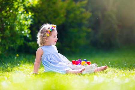 Funny little girl playing in sunny garden. Baby on Easter egg hunt. Toddler child with white basket picking colorful eggs in park. Kids play outdoors in summer. Spring fun for family with children.