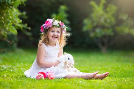 Fille jouant avec un vrai lapin dans le jardin ensoleillé. Enfant et lapin à la chasse aux oeufs de Pâques dans la fleur prairie. kid enfant alimentation animal de compagnie. Les enfants et les animaux domestiques jouent. Fun et de l'amitié pour les animaux et les enfants.