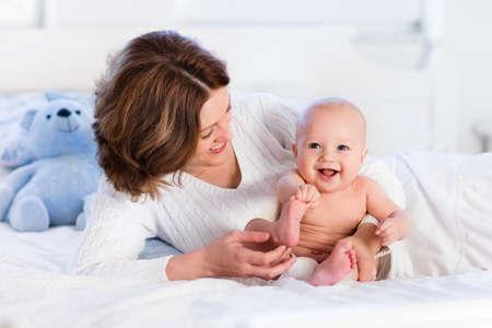 Moeder en kind op een witte bed. Moeder en baby jongen in luier spelen in het zonnige slaapkamer. Ouder en klein kind ontspannen thuis. Gezin plezier samen. Beddengoed en textiel voor baby kwekerij.