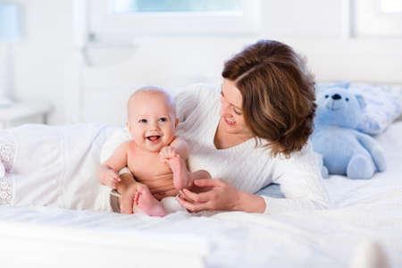 lactante: Madre y niño en una cama blanca. Mamá y bebé en pañales jugando en el dormitorio soleado. Padres y niño descansando en su casa. Familia que se divierten juntos. Ropa de cama y textil para la guardería infantil.
