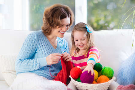 knitting: Mother and daughter knitting woolen scarf. Mom teaching child to knit. Crafts and hobby for parents and kids. Toddler girl kid with wool yarn in a basket. Knitted clothing for family with children. Stock Photo