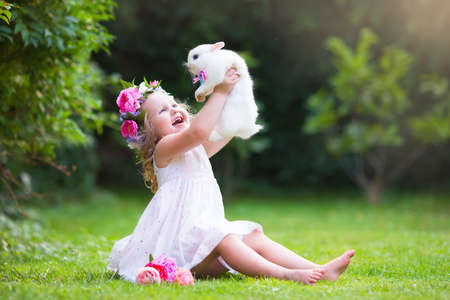 Girl playing with real rabbit in sunny garden. Child and bunny on Easter egg hunt in flower meadow. Toddler kid feeding pet animal. Kids and pets play.  Fun and friendship for animals and children.
