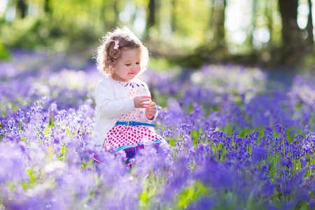 Spelen van het meisje in het zonnige bloeiende tuin. Baby op Pasen eieren zoeken in Blue Bell bloemenweide. Peuter kind plukken Bluebell bloemen. Kinderen spelen buiten. Spring leuk voor gezin met kinderen.
