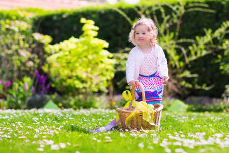 egg hunt: Little girl playing in sunny garden. Baby on Easter egg hunt in flower meadow. Toddler child with decorated basket picking colorful eggs, chocolate and sweets. Kids play outdoors. Fun for children. Stock Photo